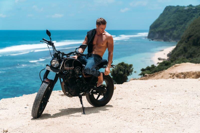 有完善的赤裸身体的性感的运动人坐摩托车、海浪和美丽的山在背景 免版税库存图片