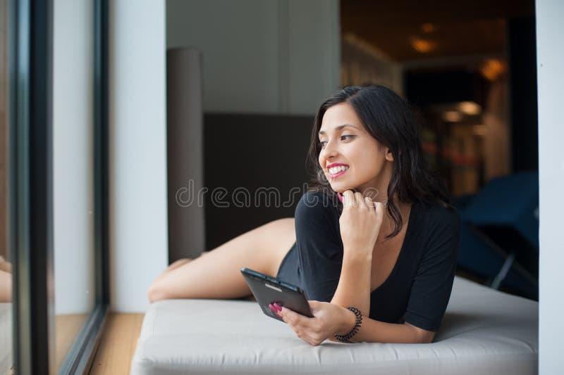 有完善的身体的妇女在说谎在床垫的黑紧身衣裤在大窗口附近在度假在休息室区域在温泉渡假胜地 免版税库存照片