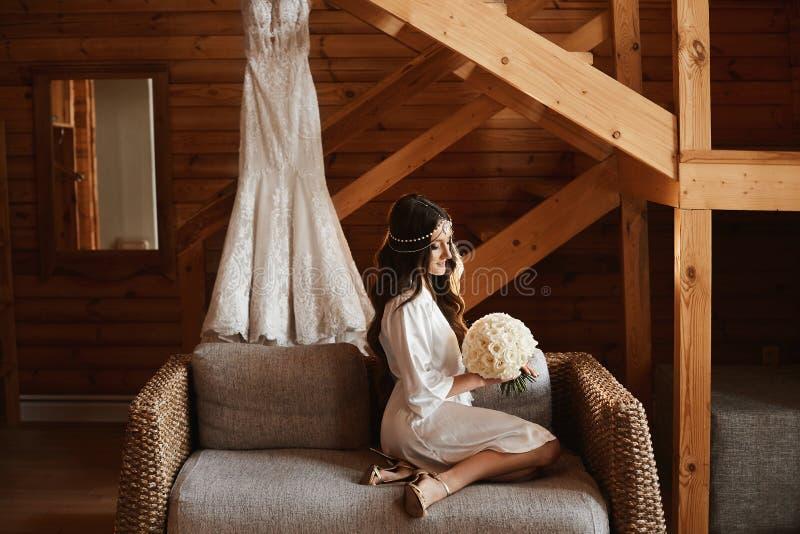 有完善的身体的美丽的年轻式样妇女在与一花束的缎peignoir在她的手上 免版税图库摄影