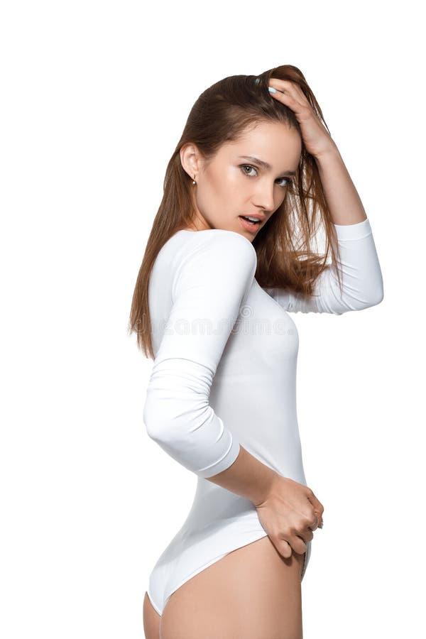 有完善的身体的美丽的性感的妇女在白色紧身衣裤 免版税库存照片