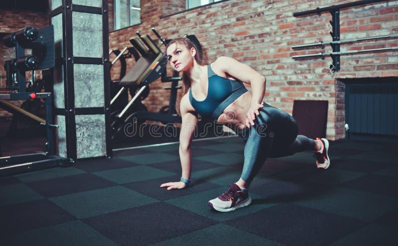 有完善的身体的运动年轻女人在运动服做腿的舒展在健身房 免版税库存照片