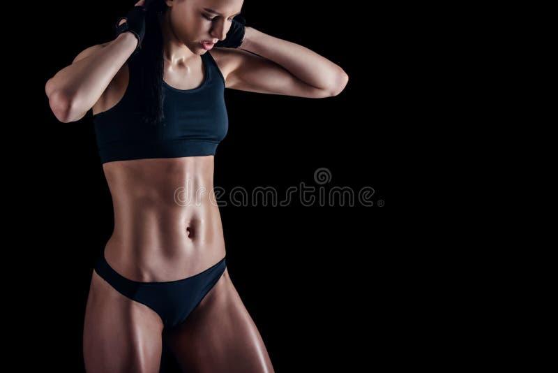 有完善的身体的运动的女性反对黑背景 运动服的健身妇女有理想的健身身体的 免版税库存照片