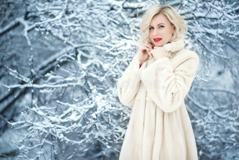 有完善的迷人的白肤金发的夫人做在多雪的树中的佩带的豪华白色摇摆毛皮大衣身分 免版税图库摄影