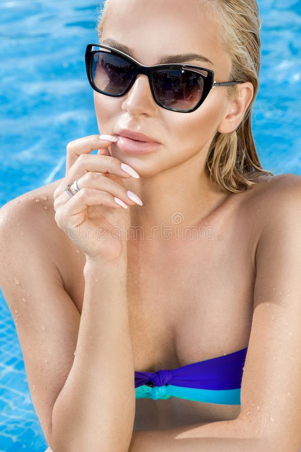 有完善的面孔的美丽的现象惊人的典雅的豪华性感的白肤金发的式样妇女在站立在po的比基尼泳装和太阳镜 免版税库存图片