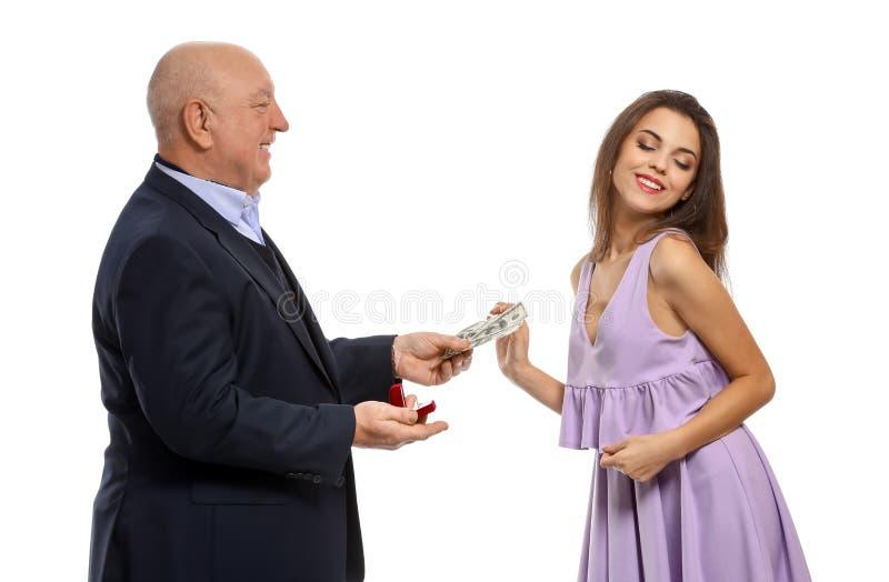 有定婚戒指和金钱的老人提议对白色背景的年轻女人 权宜婚姻 免版税库存图片