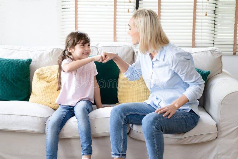 有宜人的微笑的愉快的微笑的母亲画象和女儿愉快地招呼并且互相给拳头爆沸,有正面 免版税库存照片