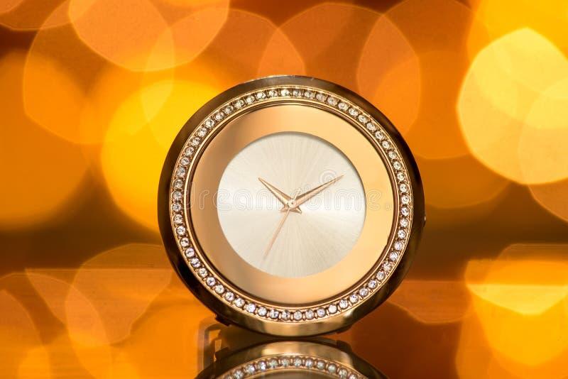 有宝石的金黄手表在迷离欢乐背景 免版税库存图片