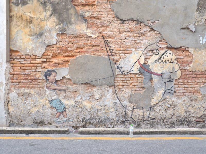有宠物恐龙的,街道艺术小男孩在乔治城市,槟榔岛,马来西亚 库存图片