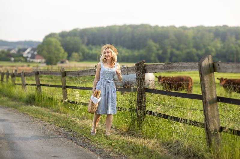 有审阅与吃草母牛的领域的袋子的村庄女孩牛奶和面包 夏天农村生活在德国 免版税库存图片