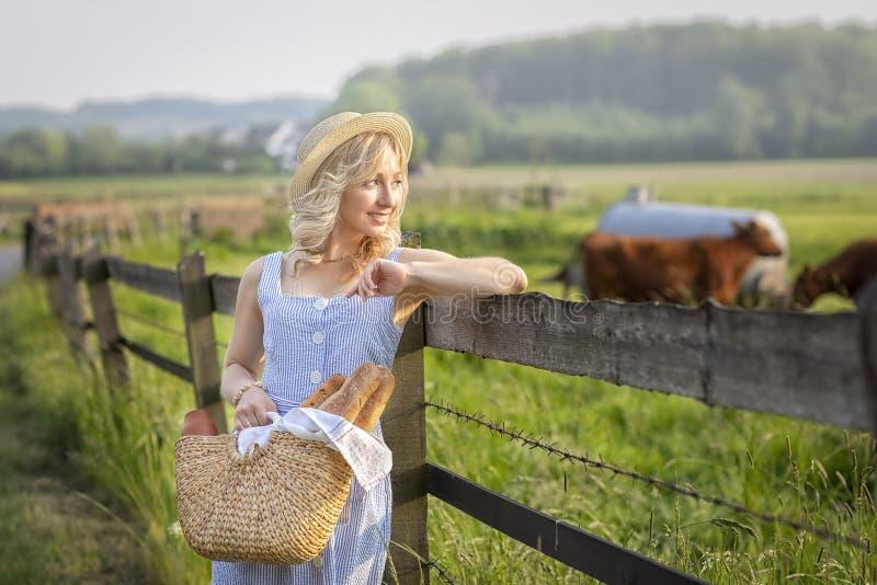有审阅与吃草母牛的领域的袋子的村庄女孩牛奶和面包 夏天农村生活在德国 免版税库存照片