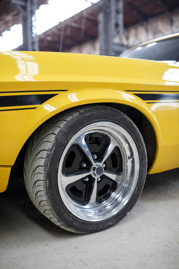 有室内合金轮子的黄色老肌肉汽车 库存照片