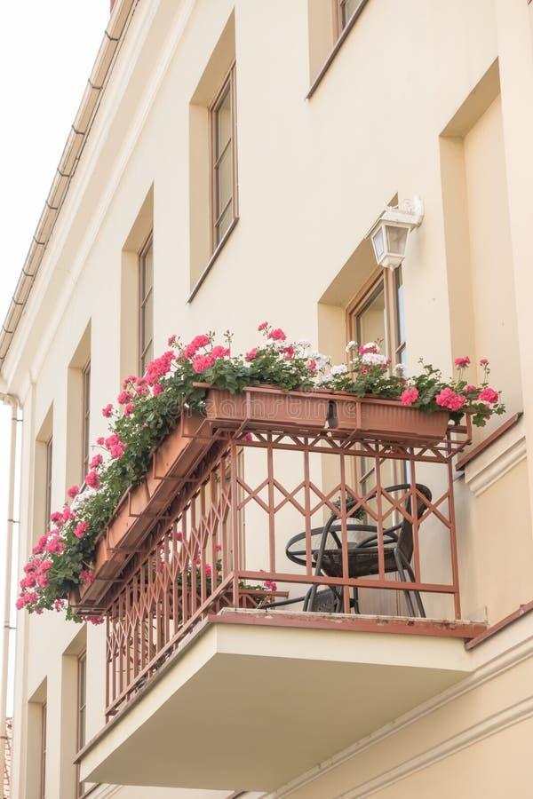 有室外家具、照明设备和花的小舒适阳台 免版税库存图片