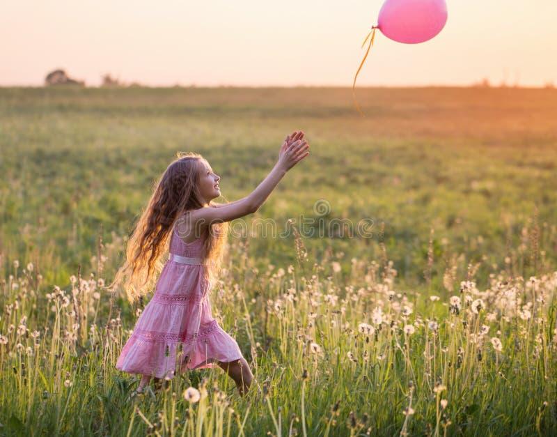 有室外桃红色的气球的女孩 免版税图库摄影