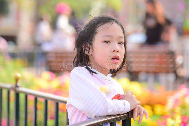 有室外桃红色的花田的逗人喜爱的亚裔女孩 库存图片
