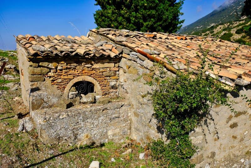 有室外烘烤烤箱的老希腊山村石头议院 库存图片