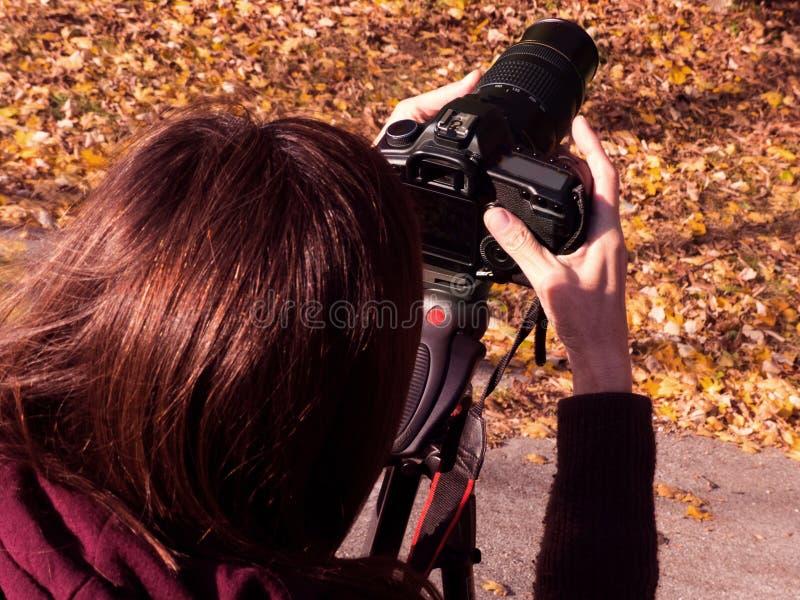 有室外的数字照相机的妇女摄影师 免版税库存照片