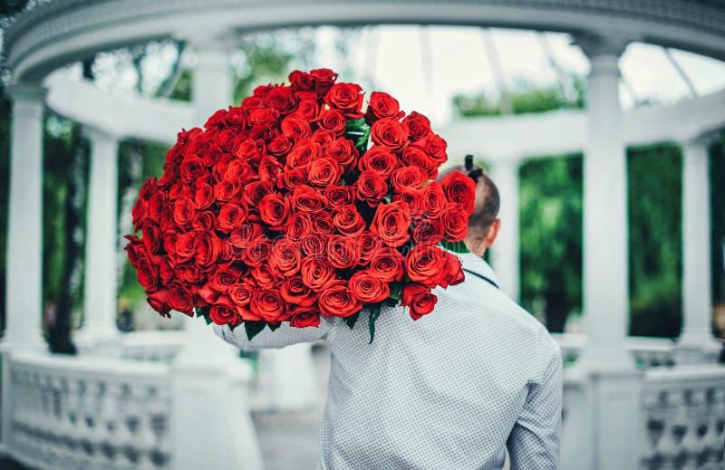 有室外的玫瑰大花束的人  免版税库存照片