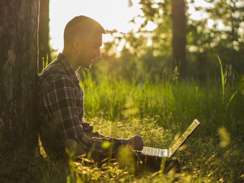 有室外的膝上型计算机的微笑的年轻人 免版税库存图片