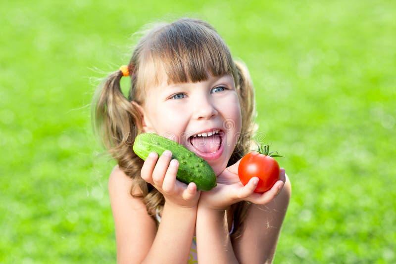 有室外的菜的可爱的小女孩 免版税图库摄影