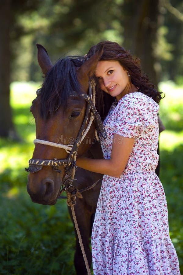 有室外的马的美丽的少妇 免版税库存图片