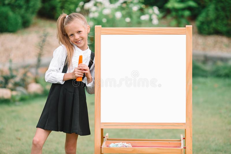 有室外的黑板的愉快的矮小的女小学生 免版税图库摄影