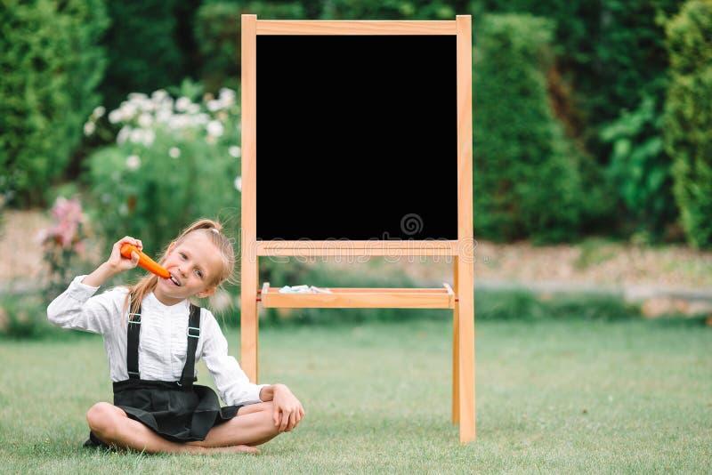 有室外的黑板的愉快的矮小的女小学生 库存图片