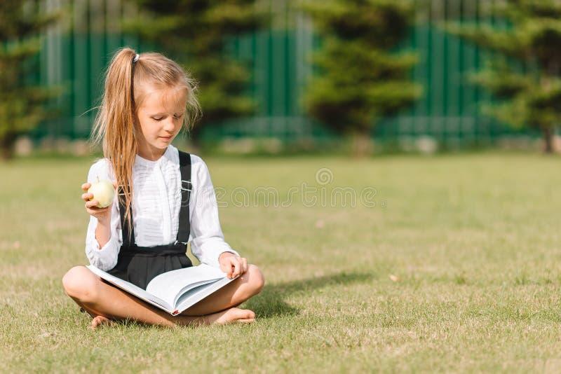 有室外的黑板的愉快的矮小的女小学生 图库摄影