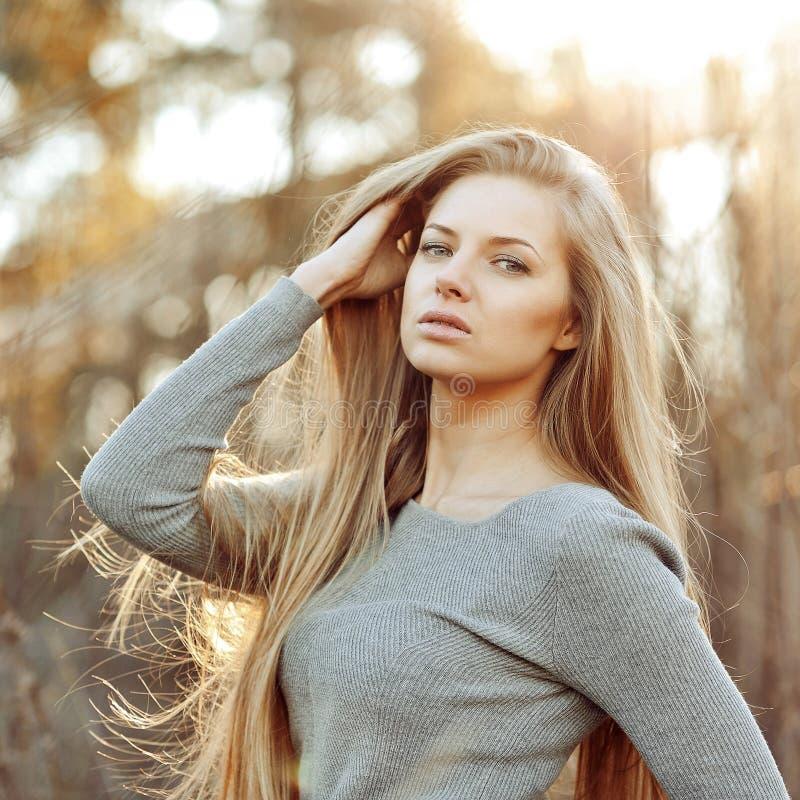 有室外长的别致的头发的美丽的白肤金发的妇女- 免版税库存图片