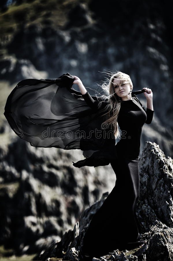 有室外黑的礼服的时兴的美丽的妇女 免版税库存图片
