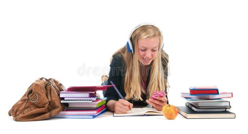 有家庭作业和smarphone的青少年的女孩 免版税图库摄影