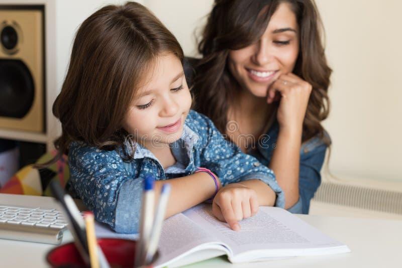 有家庭作业的母亲帮助的孩子 免版税库存照片