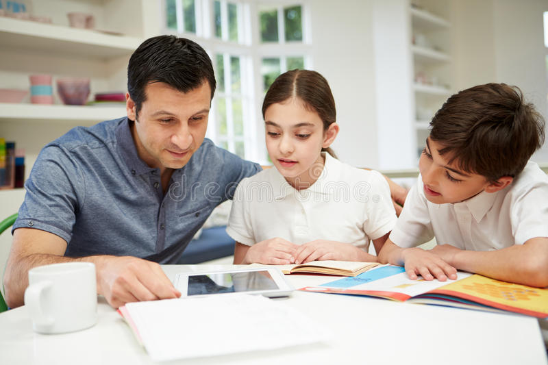 有家庭作业的父亲帮助的孩子 免版税库存照片