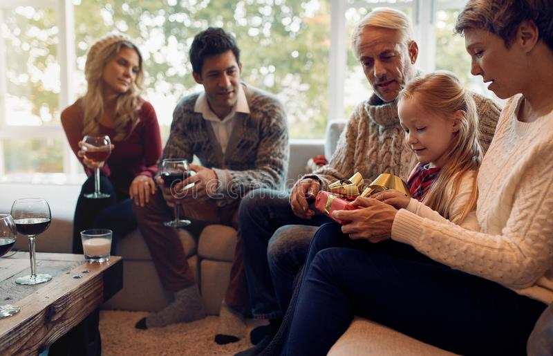 有家庭开头圣诞节礼物的小女孩 库存照片