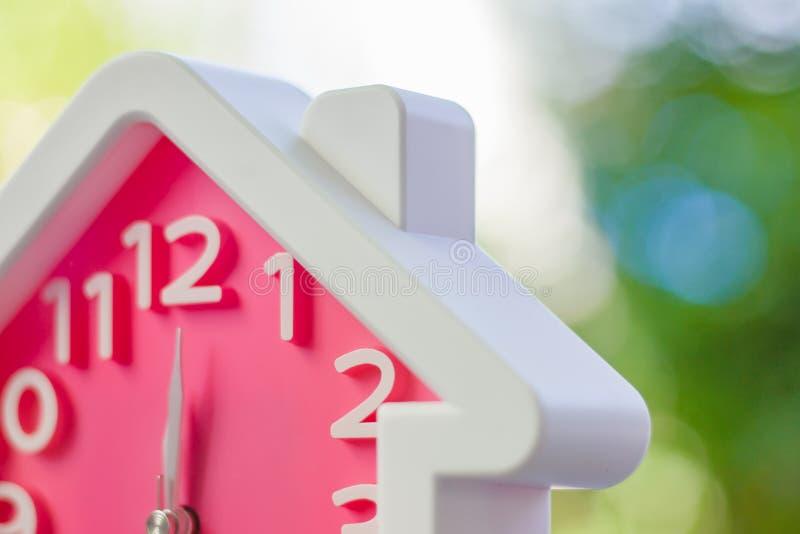 有家庭形状的桃红色时钟在12个o' 反对被弄脏的自然的时钟 图库摄影