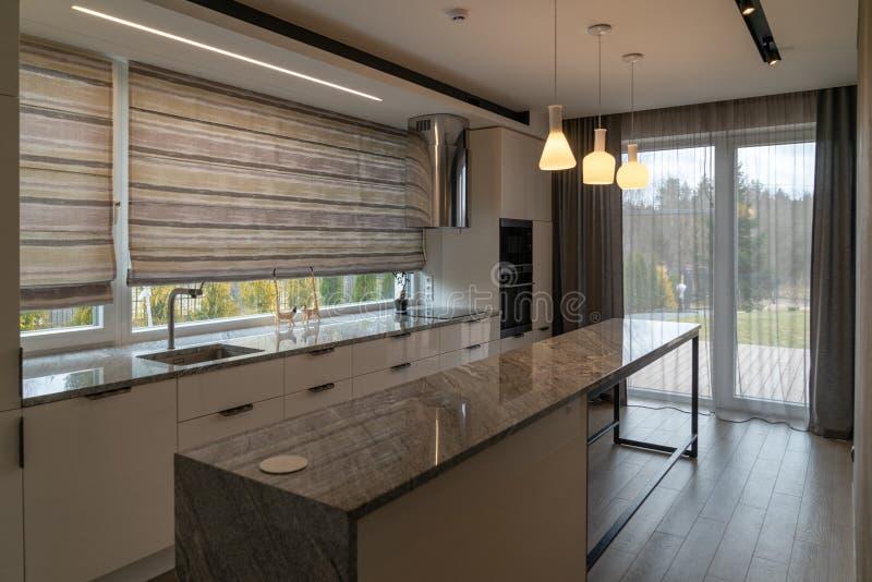 有家用家具的现代美丽的厨房在豪华家 库存图片