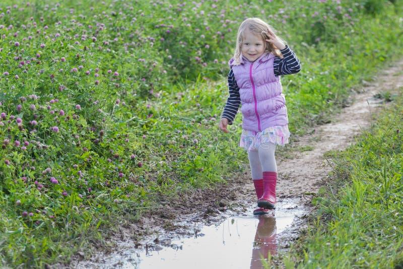 有宽松公平的头发的微笑的白肤金发的女孩走在土路的下雨在紫色三叶草花草甸的水坑 免版税库存图片
