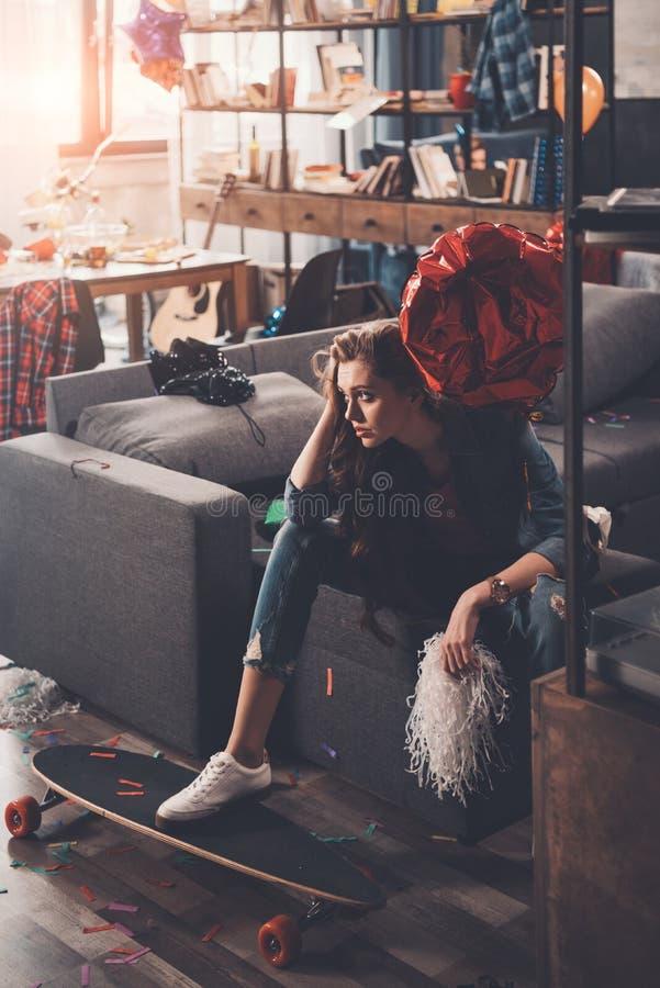 有宿酒的年轻人生气妇女坐长沙发在杂乱屋子里 免版税库存图片