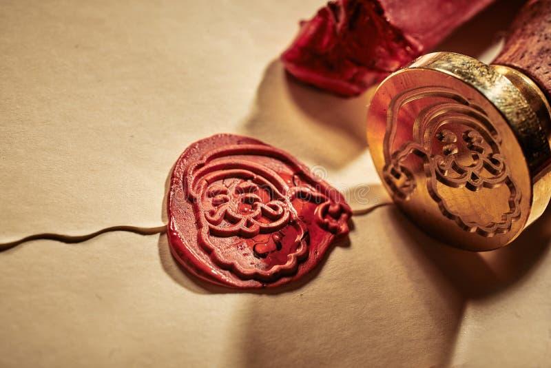 有密封一个装饰葡萄酒信件和信封在关闭的父亲圣诞节的面孔的红色蜡封印看法与黄铜 库存图片