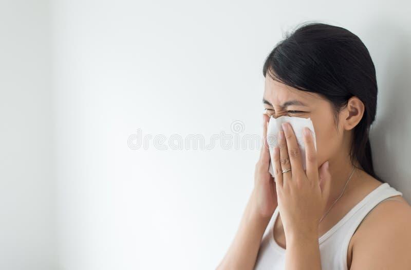 有寒冷吹的亚裔妇女和流鼻水在家、打喷嚏病的健康的妇女,概念,关闭和选择聚焦 免版税库存图片