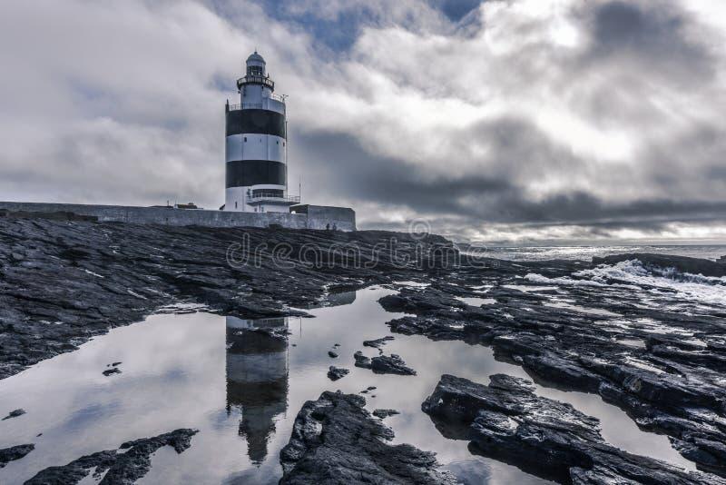 有对称反射的勾子灯塔在水,爱尔兰中 免版税库存图片