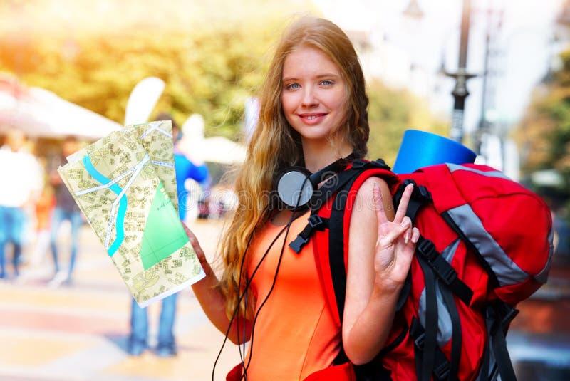 有寻找方式旅游纸地图的背包的旅行家女孩 库存照片