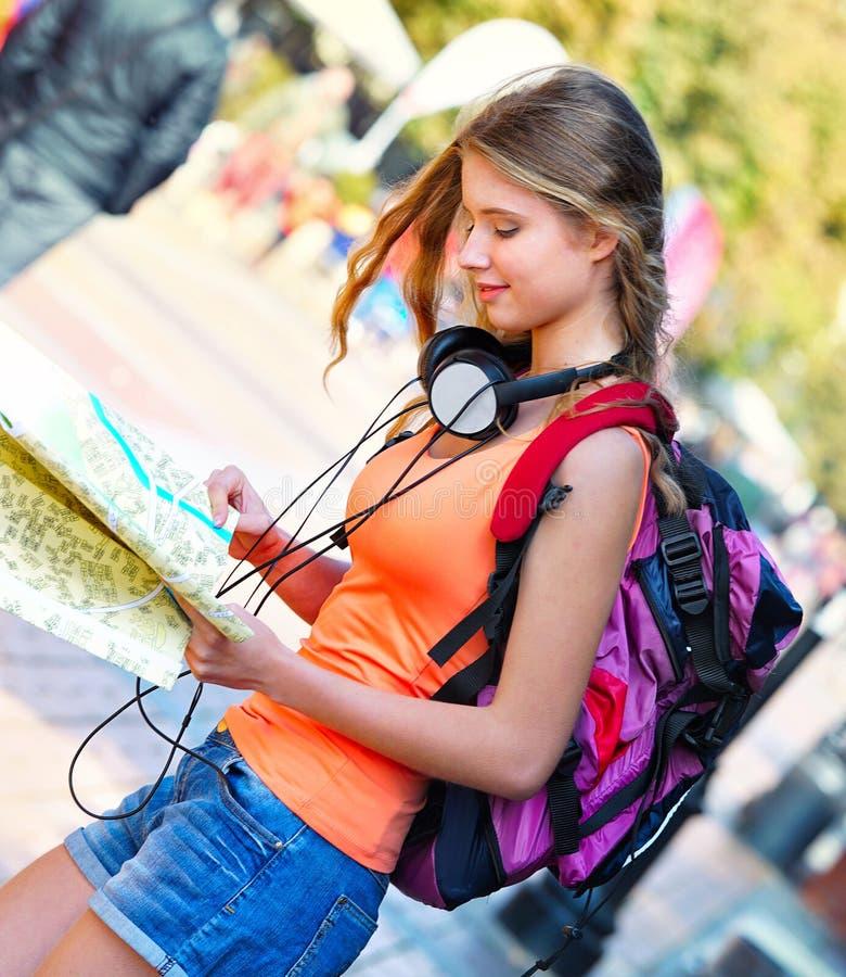 有寻找方式旅游纸地图的背包的旅行家女孩 库存图片