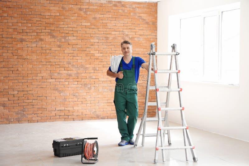 有导线的成熟电工在新的空的公寓 免版税库存照片