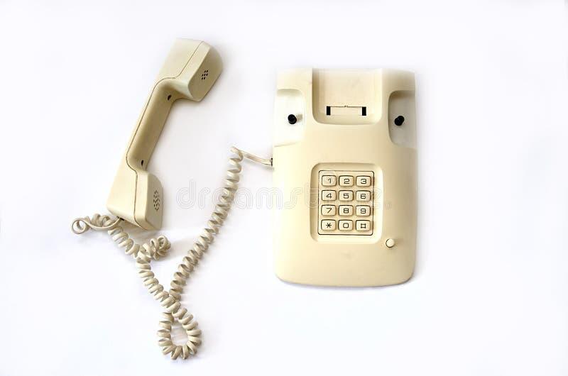 有导线管的孤立米黄老电话在白色背景说谎 库存图片