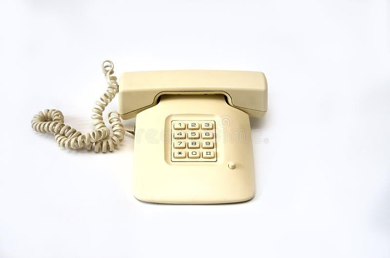有导线管的孤立米黄老电话在白色背景说谎 图库摄影