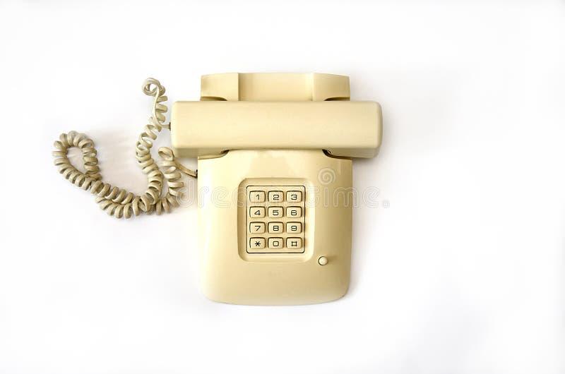 有导线管的孤立米黄老电话在白色背景说谎 免版税库存照片