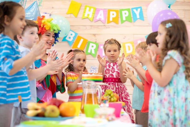 有小丑小丑拍手的孩子在与生日蛋糕的桌附近 图库摄影