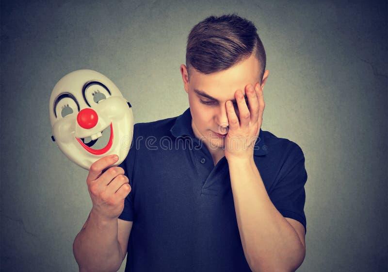 有小丑面具的沮丧的人 库存照片