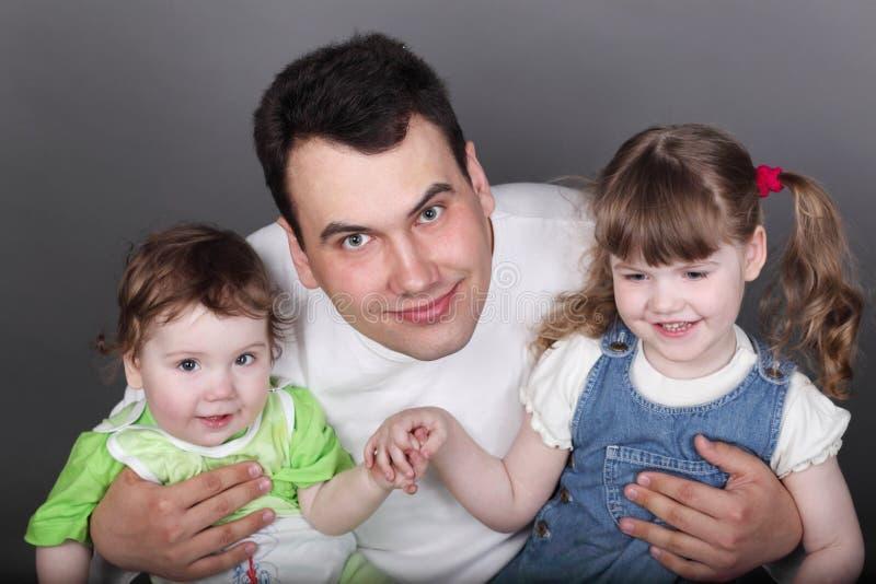 有小儿子和逗人喜爱的女儿的年轻愉快的父亲 图库摄影