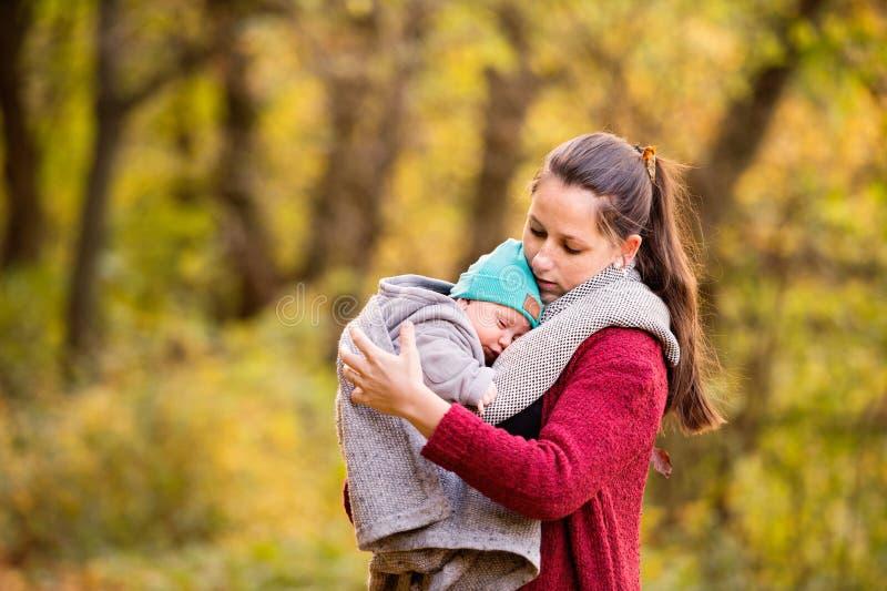 有小儿子的年轻母亲步行的在秋天森林里 库存照片